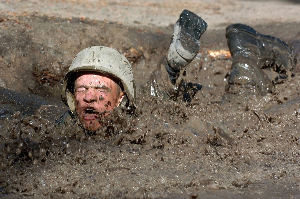 Seek Stress to Learn - Soldier crawling through deep mud